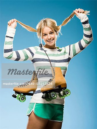 Studio portrait of young woman with roller skates Stock Photo - Premium Royalty-Free, Image code: 640-03257524
