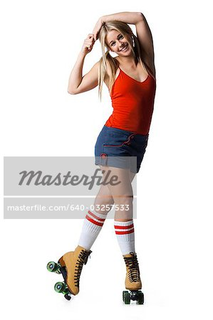Portrait of young woman roller skating Stock Photo - Premium Royalty-Free, Image code: 640-03257533