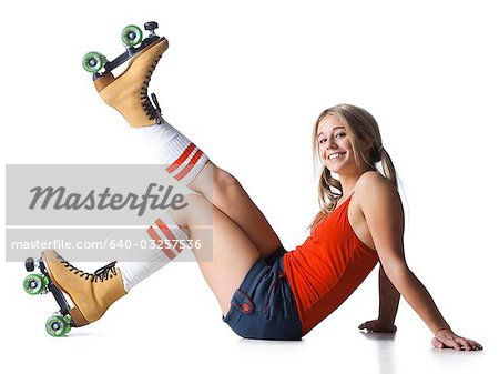 Portrait of young woman wearing roller skates Stock Photo - Premium Royalty-Free, Image code: 640-03257536