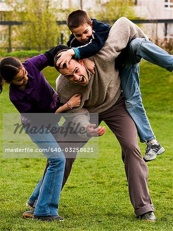 Father play fighting with son and daughter Stock Photo - Premium Royalty-Free, Image code: 640-03258621