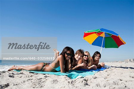 Four adults lying on the beach Stock Photo - Premium Royalty-Free, Image code: 640-03258693