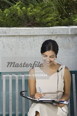 Woman working sitting on bench Stock Photo - Premium Royalty-Free, Image code: 640-03259504