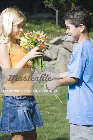 Boy giving girl flowers Stock Photo - Premium Royalty-Free, Image code: 640-03261020