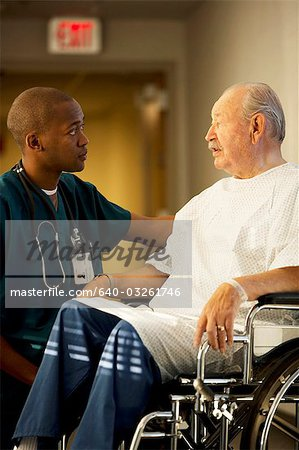 Mature man in wheelchair with doctor and nurse Stock Photo - Premium Royalty-Free, Image code: 640-03261746