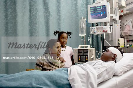 Family watching boy in hospital bed with head bandages Stock Photo - Premium Royalty-Free, Image code: 640-03261816
