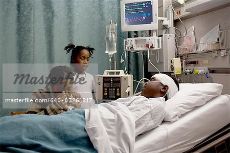 Family watching boy in hospital bed with head bandages Stock Photo - Premium Royalty-Free, Image code: 640-03261817