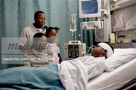 Family watching boy in hospital bed with head bandages Stock Photo - Premium Royalty-Free, Image code: 640-03261818