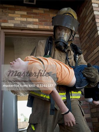 Fire fighter rescuing child Stock Photo - Premium Royalty-Free, Image code: 640-03262137