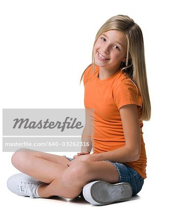 Girl sitting with arms and legs crossed Stock Photo - Premium Royalty-Free, Image code: 640-03262316