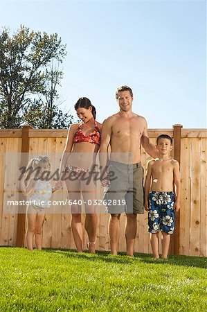 Family in bathing suits holding hands in yard Stock Photo - Premium Royalty-Free, Image code: 640-03262819