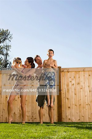 Family in bathing suits holding hands in yard Stock Photo - Premium Royalty-Free, Image code: 640-03262820