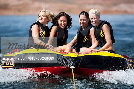 Four women on inner tube wearing life jackets Stock Photo - Premium Royalty-Free, Image code: 640-03263189
