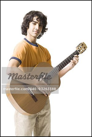 Boy playing the guitar Stock Photo - Premium Royalty-Free, Image code: 640-03263388