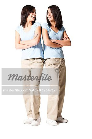 Sisters back to back with arms crossed Stock Photo - Premium Royalty-Free, Image code: 640-03264717