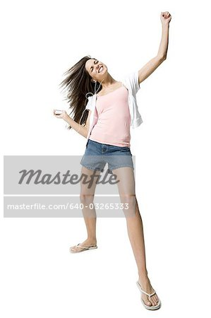 Woman listening to MP3 player and dancing Stock Photo - Premium Royalty-Free, Image code: 640-03265333