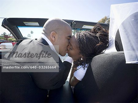 Rear view of a newlywed couple kissing each other in a car Stock Photo - Premium Royalty-Free, Image code: 640-03265664