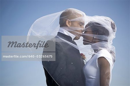 Profile of a newlywed couple kissing each other Stock Photo - Premium Royalty-Free, Image code: 640-03265675