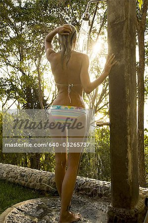 Rear view of a young woman under a shower Stock Photo - Premium Royalty-Free, Image code: 640-03265737
