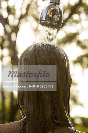 Rear view of a young woman under a shower Stock Photo - Premium Royalty-Free, Image code: 640-03265739