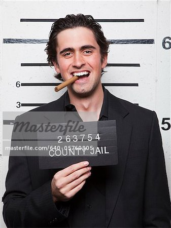 Studio mugshot of young man smoking cigar Stock Photo - Premium Royalty-Free, Image code: 640-05760905