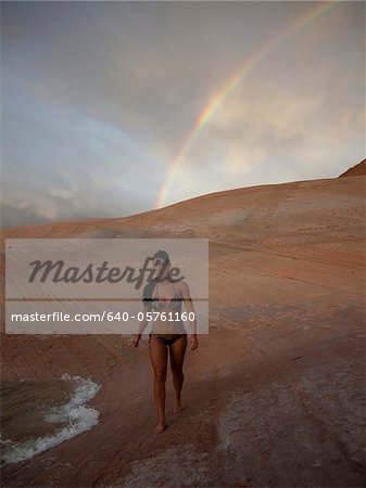 USA, Utah, Lake Powell, Young woman wearing bikini and walking, rainbow in the background Stock Photo - Premium Royalty-Free, Image code: 640-05761160