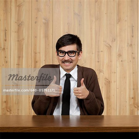 Portrait of businessman giving thumbs up Stock Photo - Premium Royalty-Free, Image code: 640-05761171