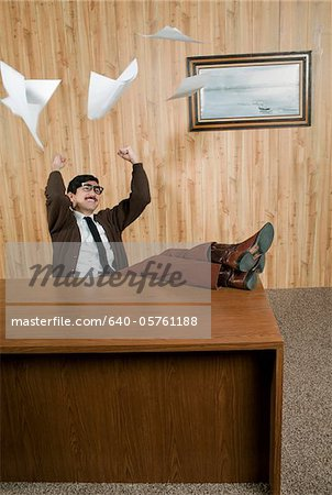 Successful businessman throwing paperwork in office Stock Photo - Premium Royalty-Free, Image code: 640-05761188