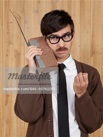 Businessman using brick mobile phone in office Stock Photo - Premium Royalty-Free, Image code: 640-05761193