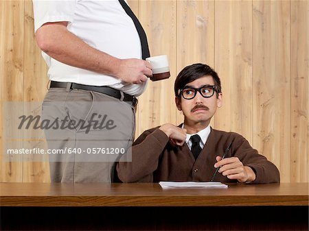 Boss by stressed businessman at desk in office Stock Photo - Premium Royalty-Free, Image code: 640-05761200