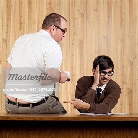 Businessman ignoring colleague at desk in office Stock Photo - Premium Royalty-Free, Image code: 640-05761202