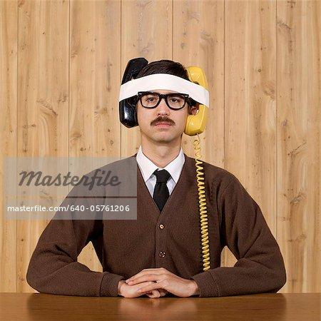 Businessman with telephones strapped to head in office Stock Photo - Premium Royalty-Free, Image code: 640-05761206