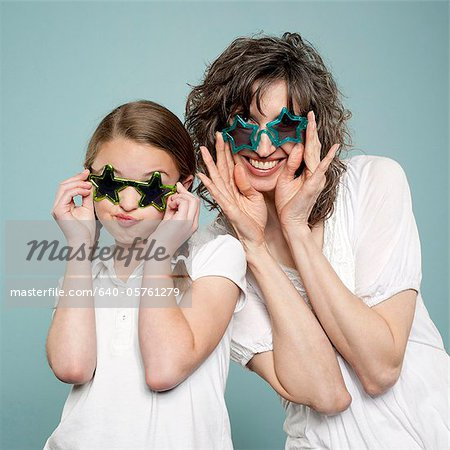 Studio shot of mother and daughter (10-11) wearing star shaped sunglasses Stock Photo - Premium Royalty-Free, Image code: 640-05761279
