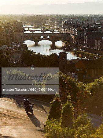 Italy, Florence, Couple with motorbike overlooking River Arno Stock Photo - Premium Royalty-Free, Image code: 640-06049914