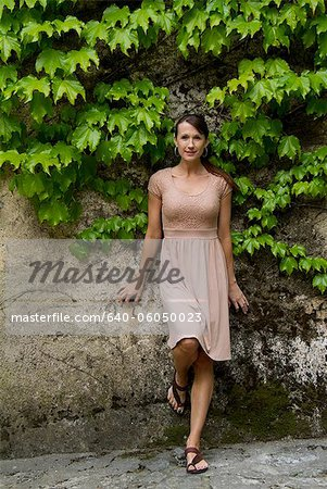Italy, Ravello, Portrait of woman in dress leaning overgrown wall Stock Photo - Premium Royalty-Free, Image code: 640-06050023