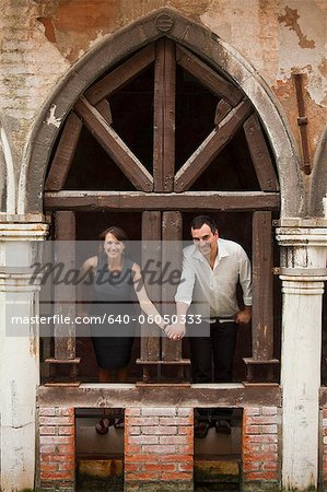 Italy, Venice, Couple standing in arcade Stock Photo - Premium Royalty-Free, Image code: 640-06050333