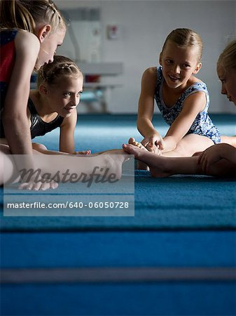 USA, Utah, Orem, Girls (8-11) stretching in gym Stock Photo - Premium Royalty-Free, Image code: 640-06050728