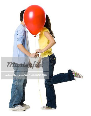 couple kissing behind a red balloon Stock Photo - Premium Royalty-Free, Image code: 640-06051396