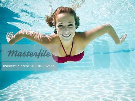 teenage girl in a bathing suit swimming in a pool Stock Photo - Premium Royalty-Free, Image code: 640-06052113