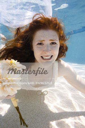 USA, Utah, Orem, Portrait of young bride with bouquet under water Stock Photo - Premium Royalty-Free, Image code: 640-06963263