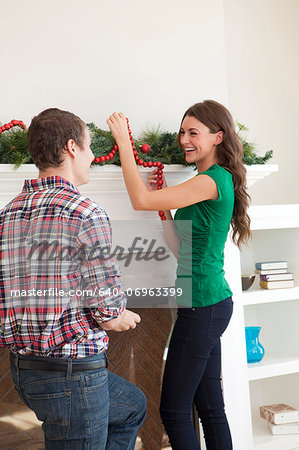 Smiling couple decorating room for Christmas Stock Photo - Premium Royalty-Free, Image code: 640-06963399