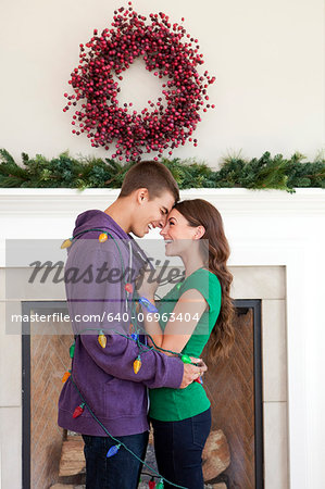 Smiling couple in room decorated for christmas Stock Photo - Premium Royalty-Free, Image code: 640-06963404