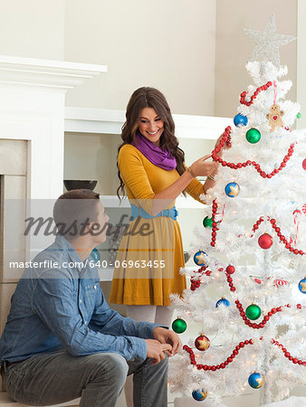Happy young couple decorating Christmas tree Stock Photo - Premium Royalty-Free, Image code: 640-06963455