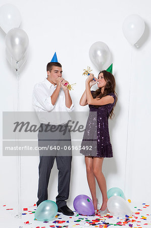Young couple blowing horns at party Stock Photo - Premium Royalty-Free, Image code: 640-06963492