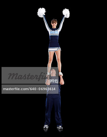 Teenage sportsman(16-17) holding aloft teenage cheerleader girl (16-17) Stock Photo - Premium Royalty-Free, Image code: 640-06963614