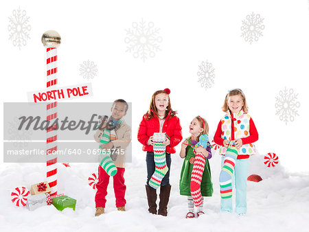 Group of kids (18-23months, 4-5,6-7) standing next to North Pole sign Stock Photo - Premium Royalty-Free, Image code: 640-06963745