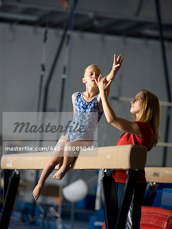 USA, Utah, Orem, coach assisting girl gymnast (10-11) on balance beam Stock Photo - Premium Royalty-Free, Image code: 640-08089047