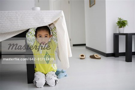 Boy hiding under table, smiling Stock Photo - Premium Royalty-Free, Image code: 642-01732839
