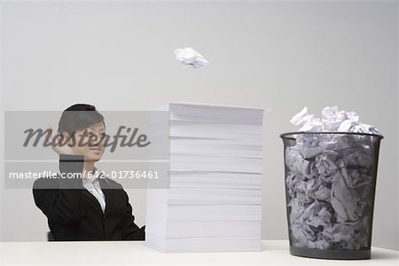 Business woman throwing paper to garbage bin Stock Photo - Premium Royalty-Free, Image code: 642-01736461