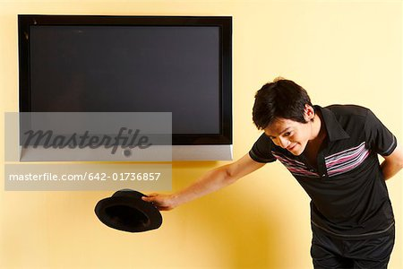 Fashionable young man bowing in front of TV Stock Photo - Premium Royalty-Free, Image code: 642-01736857