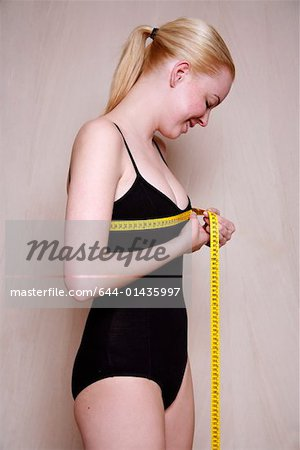 Woman measuring her chest Stock Photo - Premium Royalty-Free, Image code: 644-01435997